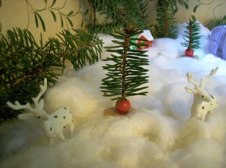 A small tree in a miniature Christmas display.