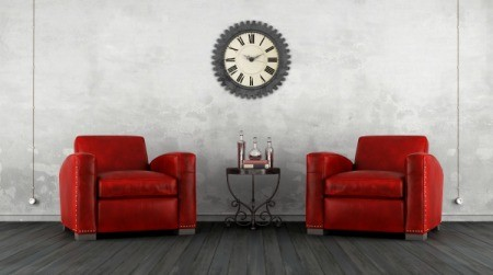A pair of red leather chairs in a white room.