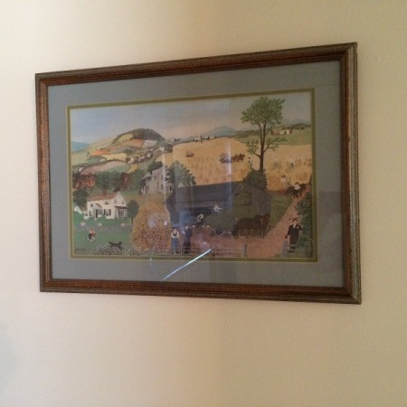 A large picture with a wooden frame, hanging on a wall.