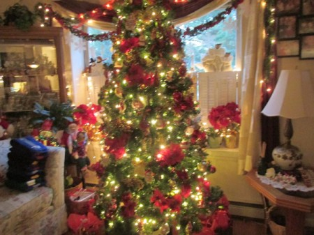 A decorated and lighted Christmas tree inside a living room.