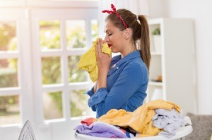 A woman smelling her clean clothes with pleasure.