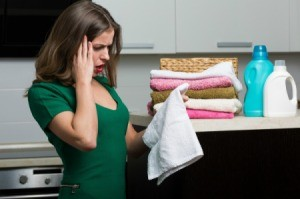 A woman looking at a mysterious grease stain on her laundered clothing.