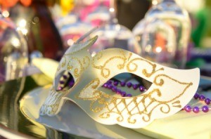 A mask sitting on a decorated table at a masquerade.