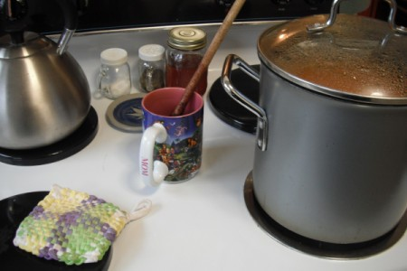 A coffee cup being used as a spoon rest on a stove.
