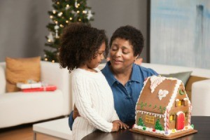 A grandmother helping her granddaughter make a gingerbread house.