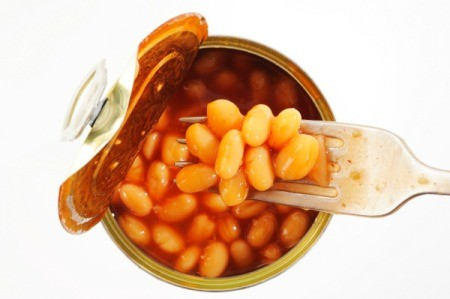 A open can of baked beans with a fork.