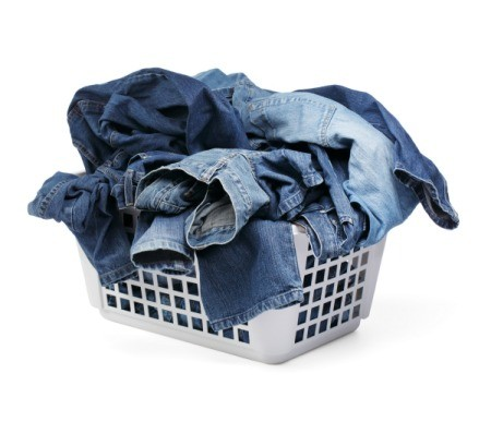 A laundry hamper of filled with jeans.