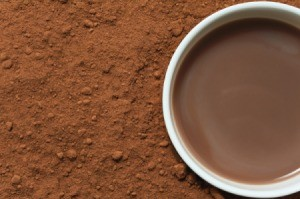 A cup of cocoa surrounded by cocoa powder.