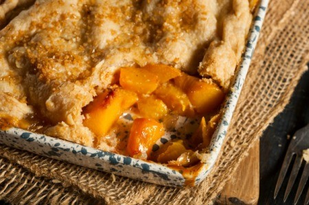 A pan of peach cobbler with a serving removed.