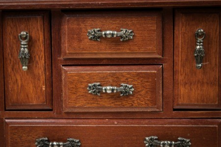 An antique dresser with many drawers.