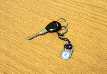 key attached to fob lying on wood grain surface