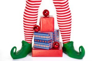 Striped elf legs over a pile of presents.