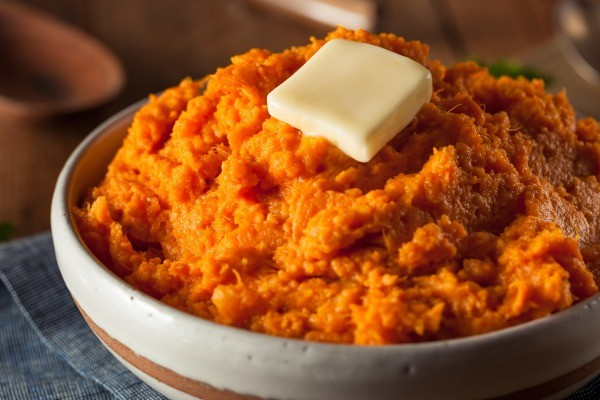 bowl of mashed sweet potatoes with a pat of butter