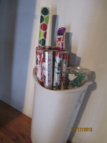 Gift wrap stored in a tall garbage canl.
