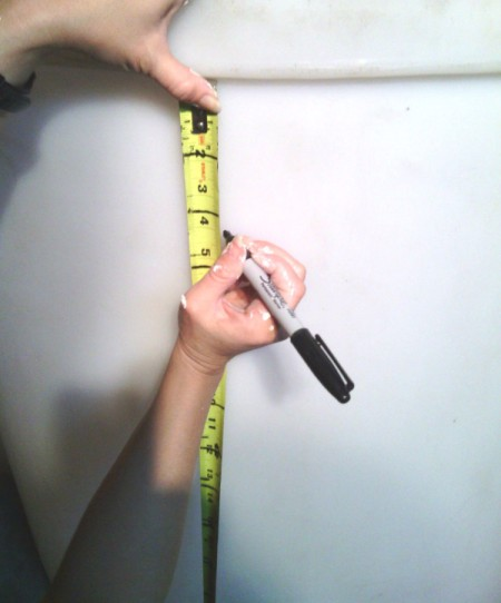 using a measuring tape and Sharpie to mark divisions on cylinder