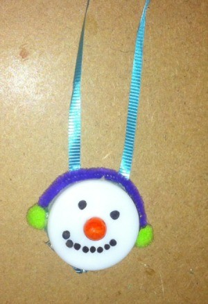 snowman with green muffs and blue ribbon