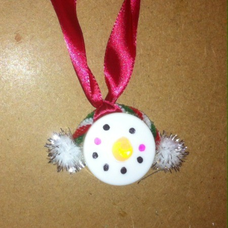 snowman with white muffs and red ribbon