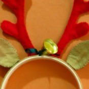 A headband that looks like reindeer antlers and ears with a decorative bell.