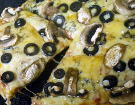 A cheese pizza with toppings added