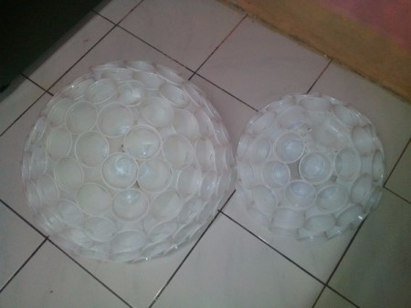 two half spheres made of plastic drinking cups lying on floor after gluing