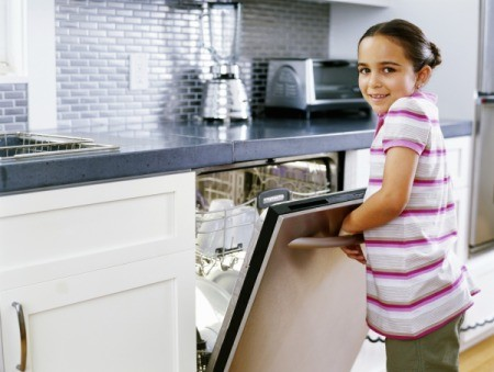 A girl opening a dishwasher at home.