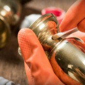 A brass candlestick being polished.