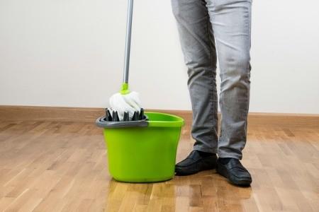 A mop and bucket on a hardwood floor.