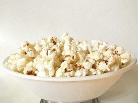 A white bowl of popcorn on a white background.
