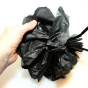 A decorative flower made out of black tissue paper.