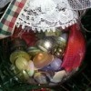 Clear plastic ornament filled with buttons and decorated with lace, netting, and ribbon hanging on the tree.