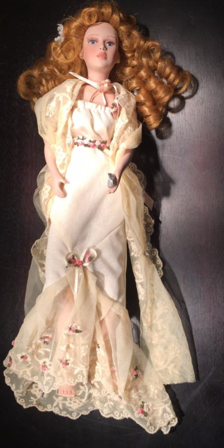 Doll with curly hair and a white formal dress.