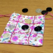 Fabric and Button Tic-Tac-Toe Game - finished game pouch with two markers on board