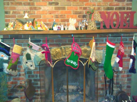 Curtain Rod For Hanging Christmas Stockings - several Christmas stockings hanging on a curtain rod beneath the fireplace mantel