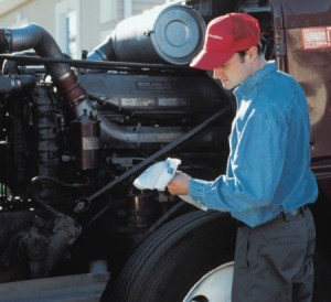 A diesel mechanic checking a trucks oil.