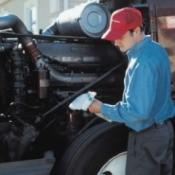 A diesel mechanic checking a trucks oil.