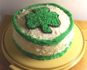 A layer cake with a shamrock in frosting on the top.