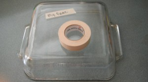 A name written on tape on the back of a casserole pan.