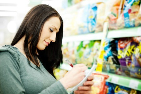 A woman grocery shopping looking at her organized shopping list.
