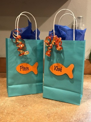 Goldfish Party Treat Bags - aqua gift bags with orange goldfish cutouts and ribbon as decorations