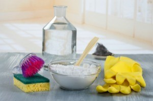 A bowl of baking soda with rubber gloves and sponge on a kitchen counter.