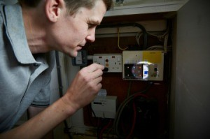 Man checks fuse box in the dark.