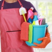 Man in an apron with a bucket of cleaning supplies.
