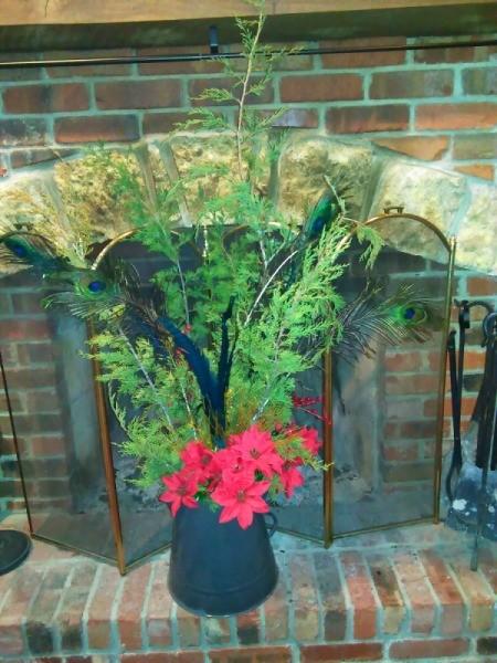DIY Holiday Centerpieces - cedar and poinsettia decoration on hearth