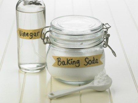 Glass bottle of Vinegar next to a jar of baking soda.