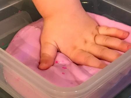 Homemade Flubber - toddler's hand mashing flubber