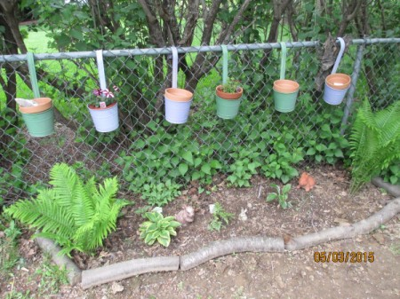 Flower Gardening in a Small Space - painted hanging pots on chain link fence with terra cotta pots inside