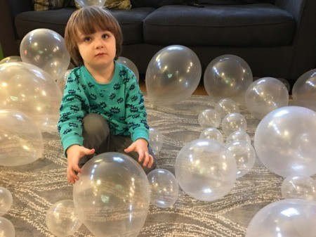 A 3 year old playing with clear balloons.