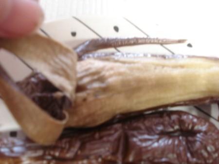 Peeling broiled eggplant.