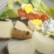 Plate with cooked potato, egg, dressing and lettuce