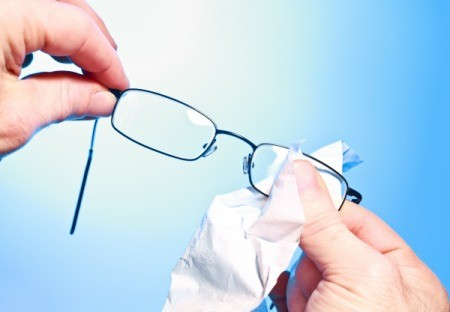 Person cleaning eyeglass lenses with a cloth.